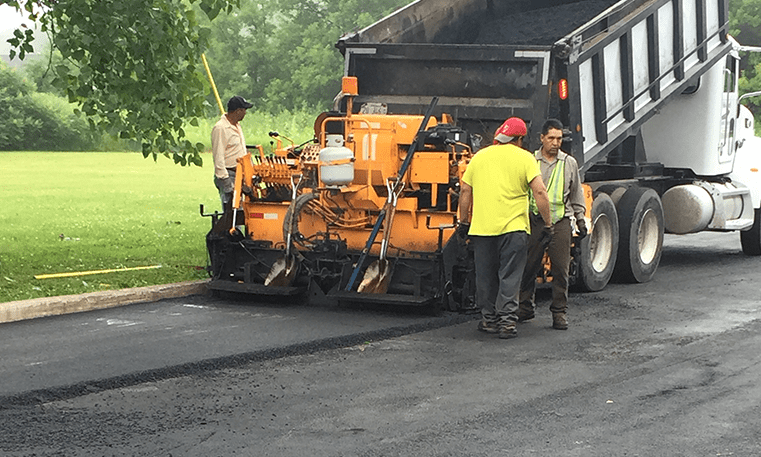 workers laying new asphalt