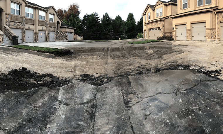 broken asphalt near houses