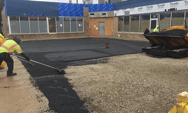 workers repairing asphalt parking lot