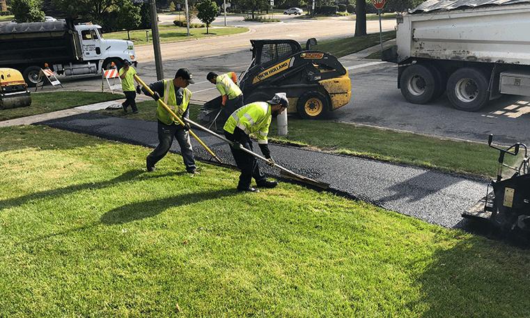 construction workers laying asphalt sidewalk