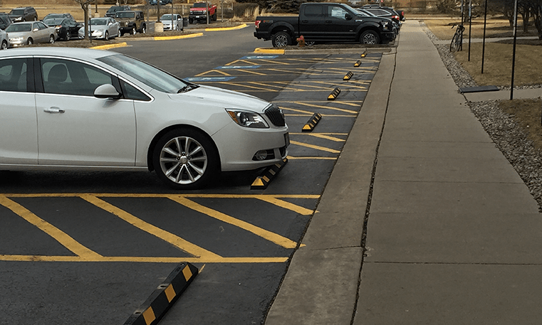 car parked in spot with bumper block