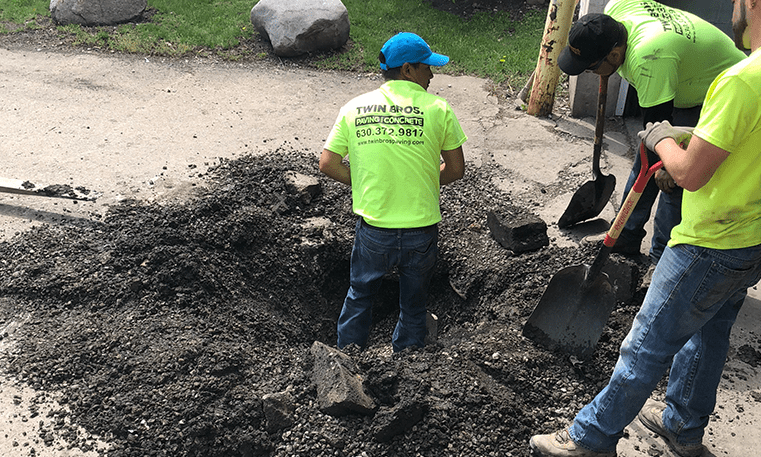 workers digging to repair catch basin