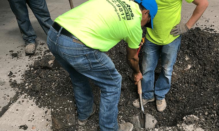 workers repairing catch basin