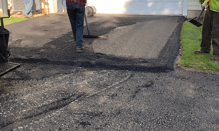 workers laying asphalt on driveway
