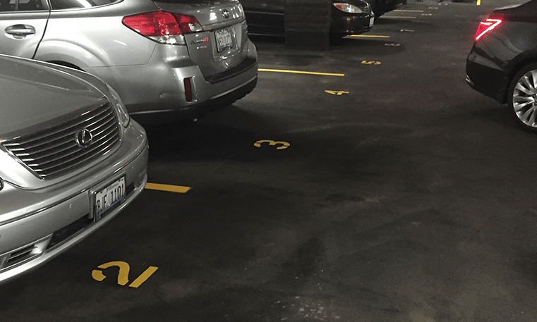 cars parked in parking garage with new striping