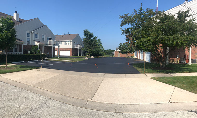 sidewalk and asphalt driveway in front of townhomes