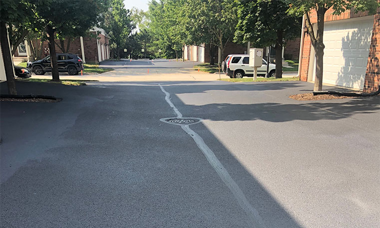 asphalt driveway in front of townhomes