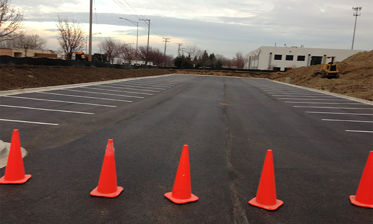 finished asphalt parking lot with construction cones