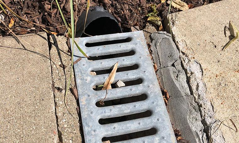 clogged drain on damaged concrete