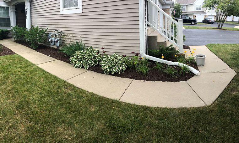new sidewalk wrapping around side of home