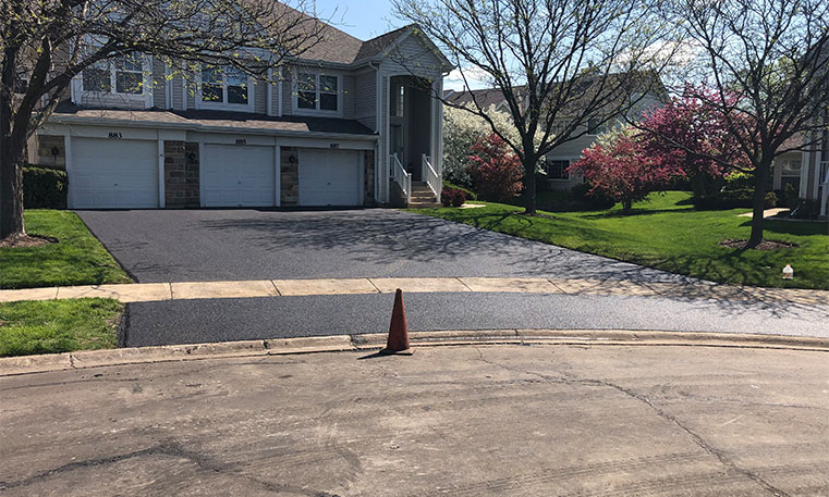 condo unit with completed asphalt driveway