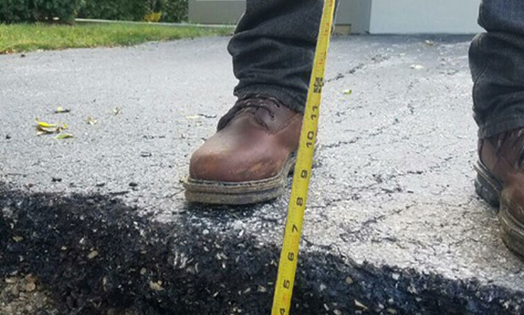 twin brothers contractor measuring asphalt