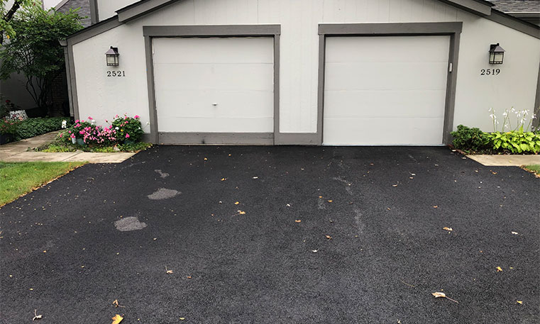 home garage and driveway after asphalt replacement