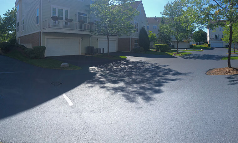 finished asphalt driveway in front of townhome