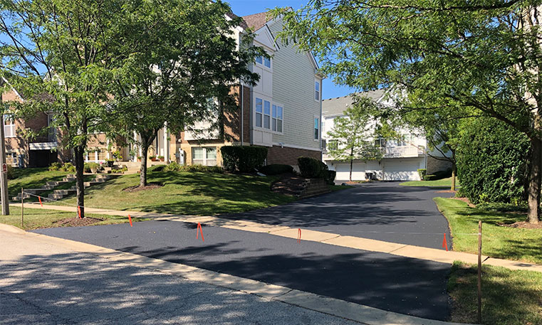 finished asphalt street and sidewalk in front of townhome association