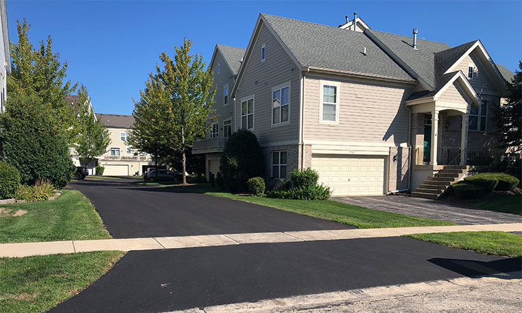 finished asphalt street in front of townhome