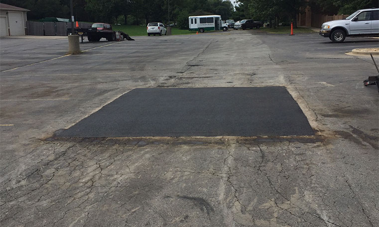 damaged asphalt with patched area