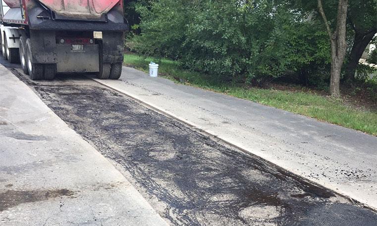 asphalt patching equipment working on damaged concrete