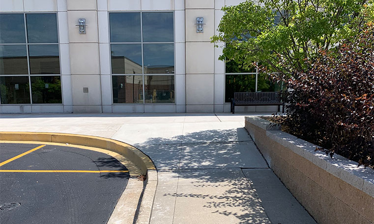 finished concrete curb and parking lot markings in front of hotel