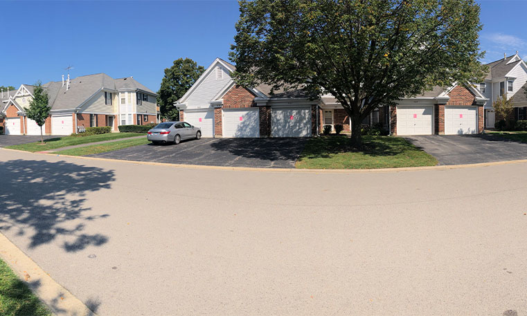 street view of home with sealcoated driveway
